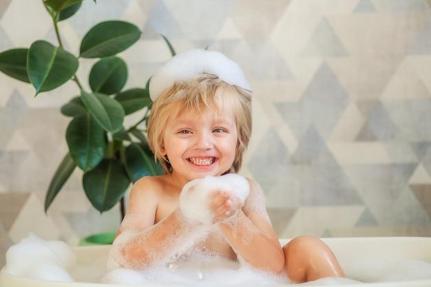 Детская гигиена. ребенок купается в большой ванне. счастливый милый мальчик 4-5 лет с пеной в волосах.
