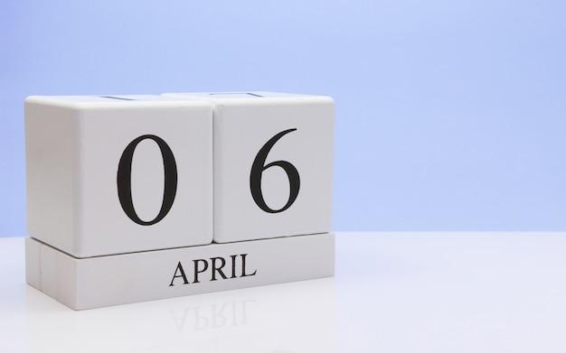 4月6日月の日06、反射を持つ白いテーブルに毎日のカレンダー