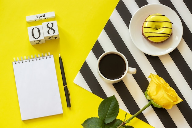 カレンダー4月8日。一杯のコーヒー、ドーナツ、バラ、メモ帳。コンセプトスタイリッシュな職場
