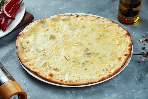 4 сырных пиццы, запеченных в дровяной печи на сером
