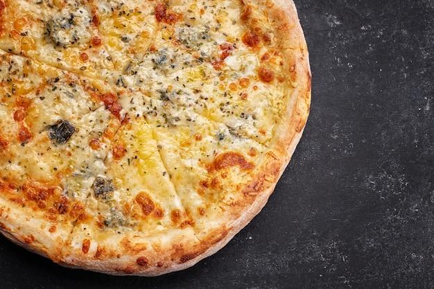 4 сырных пиццы на темном столе