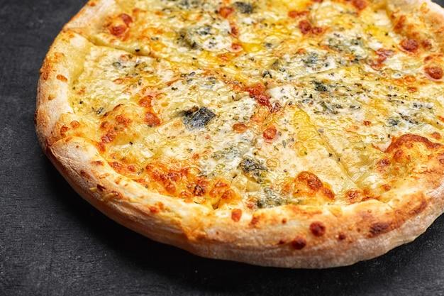 暗いテーブルに4つのチーズピザ