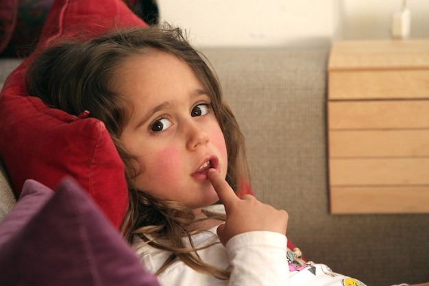A 4 and half year old girl puts a finger in her mouth