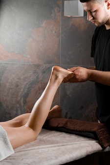 4 hands massage of legs and feet in spa. professional masseur making massage with massage oil. relaxation,