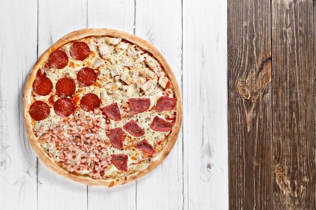さまざまな種類の肉を使ったおいしい4 in 1の新鮮なピザを木製のテーブルで提供しています。上面図。