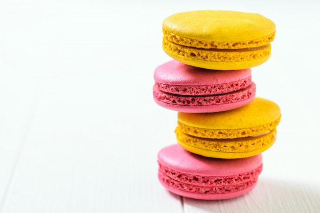 Стог 4 macaroons желтых и красных на белом деревянном столе.