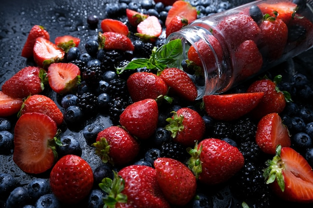 4. mix of wild forest berries on black background, collection of strawberry, blueberry and blackberry,