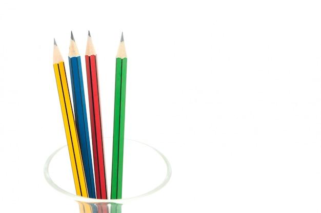 4つのシャープな色鉛筆は、教育の背景のために、白い背景の上のガラスのクローズアップ