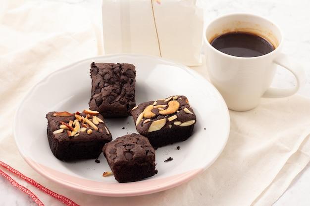 白いプレートにチョコレートチップ、アーモンド、ナッツ、白い布の上にコーヒー豆を置いた4つの正方形のダークブラウニー。ティータイム、コーヒータイム、ブレイクタイムのお菓子。