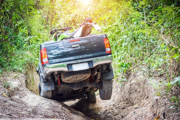 4 wheel drive with a motorcycle on the tailgate is climbing on a difficult off-road.