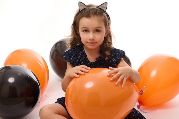 4-летняя очаровательная милая маленькая девочка в костюме ведьмы играет с черными и оранжевыми воздушными шарами, изолированными на белом фоне. концепция счастливого ребенка, весело проводящего время на традиционном сезонном мероприятии, вечеринке в честь хэллоуина
