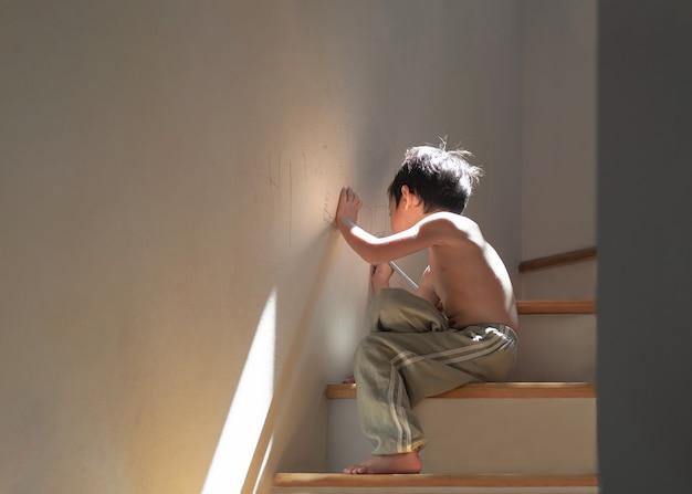 自宅で4歳のアジアの子供。自宅の壁で描画またはペイントします。