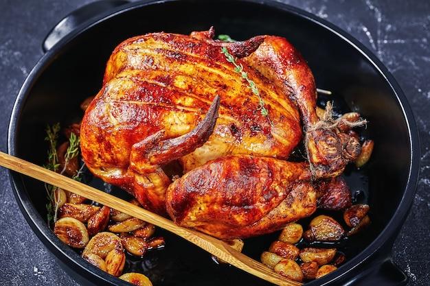 콘크리트 테이블에 검은 베이킹 접시에 40 정향 치킨, 프랑스 요리, 위에서 가로보기, 클로즈업