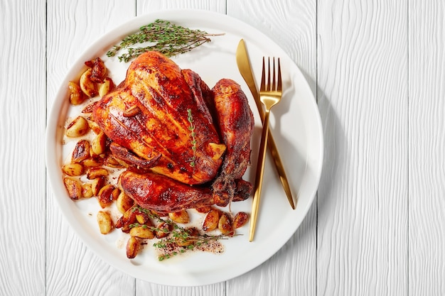 나무 테이블에 흰색 플래터에 40 정향 치킨, 프랑스 요리, 위에서 가로보기, 평평한 평지, 클로즈업, 여유 공간