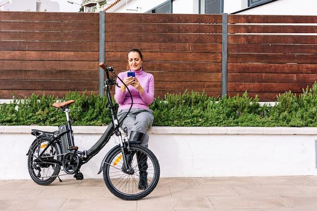 電動自転車の横で電話で話している40歳の女性
