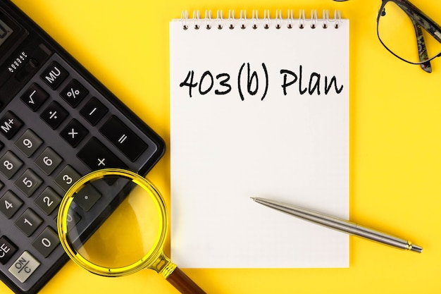 403 b plan a retirement account for certain employees. the text is written in a notebook and a calculator on a yellow wall.