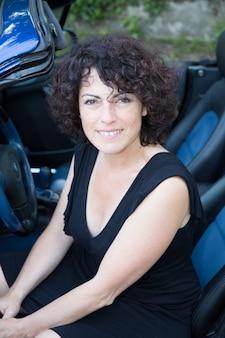 Красивая сороковая девушка 40 лет сидит в синей машине