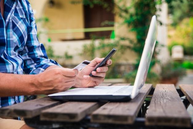 晴れた夏の日にガーデンテラスでラップトップコンピュータで作業中にクレジットカードを見て40歳の白人の男。現代的なライフスタイル - 田舎の週末とショッピングのオンラインコンセプト。