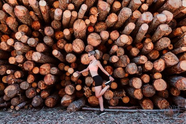 Женщина в ее 40 делает упражнения на открытом воздухе в солнечный день и растяжения