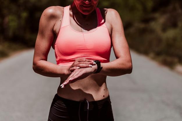 Женщина в ее 40 лет делать упражнения на улице в солнечный день и проверка смарт-часы