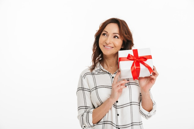 プレゼントボックスを手で押し、内部に何があるかを理解しようとして美しい笑顔で好奇心が強い女性40代、屋内の白い背景で隔離