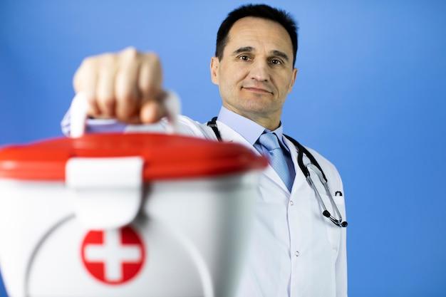 ハンサムな黒髪40代男性医師が赤十字の医療援助キットを保持しています。
