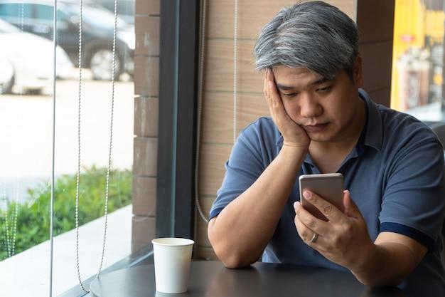 ストレスを感じ、疲れていてスマートフォンを使用している中年のアジア人男性(40歳)