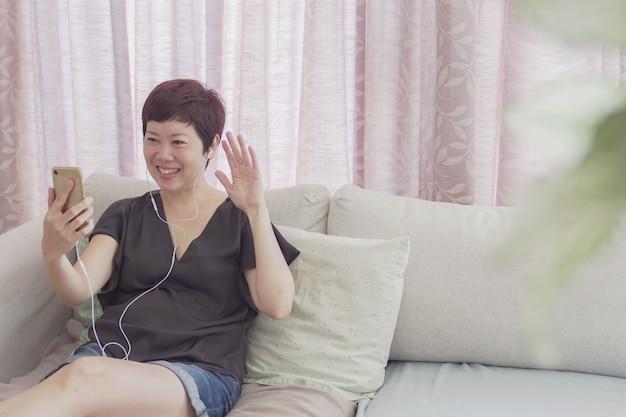 健康な中年の40代のアジアの女性の肖像画は、スマートフォンで自宅でスマートフォンを使用してフェイスタイムのビデオ通話を行い、ズーム会議のオンラインアプリを使用して、社会的距離を離し、自宅で仕事をし、リモートで仕事をするというコンセプト
