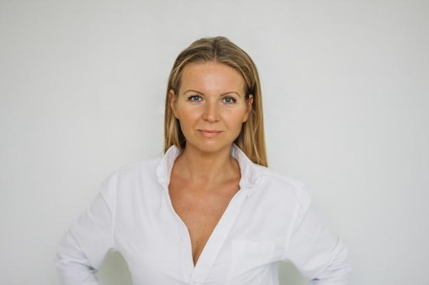 分離した白い壁の背景に白いシャツに長い髪の魅力的な金髪40年女性の肖像画