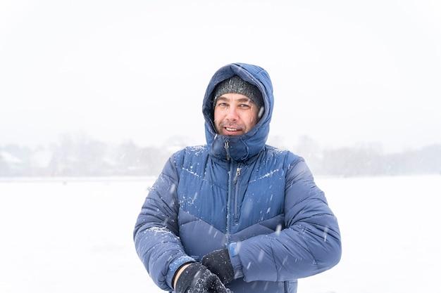 40c портрет улыбающегося человека в зимней одежде в сильный снегопад