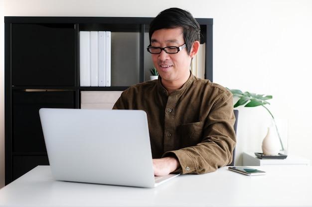 ホームオフィスやオンライン学習で現代の作業スペースでラップトップまたはコンピューターのノートブックに取り組んでいる眼鏡の40代アジア人