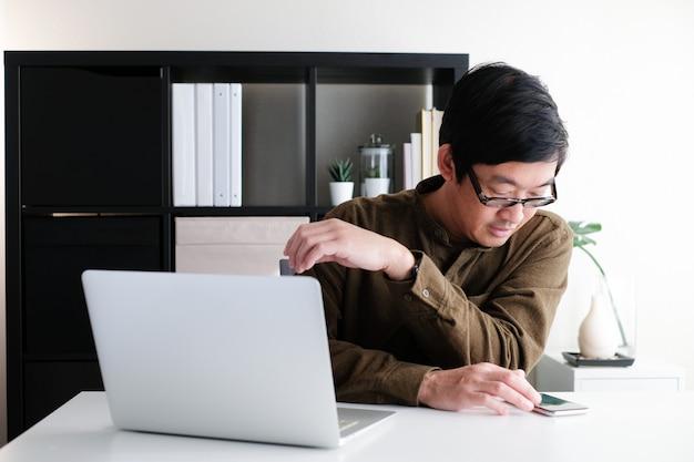 Азиатский мужчина 40-х годов в очках, работающий на ноутбуке или ноутбуке в современном рабочем пространстве в офисе дома и в режиме онлайн обучения