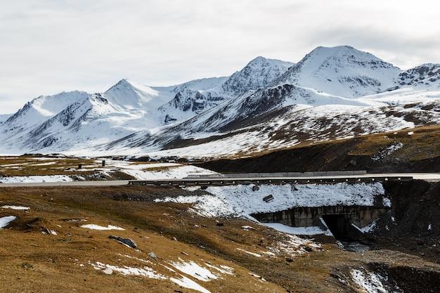 Снежные горные вершины на перевале ала бел, мост на трассе бишкек-ош м41 в кыргызстане