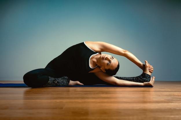 Взрослая женщина 45-55 лет в хорошей форме занимается йогой на синем фоне студии с деревянным полом на тренировочном мате