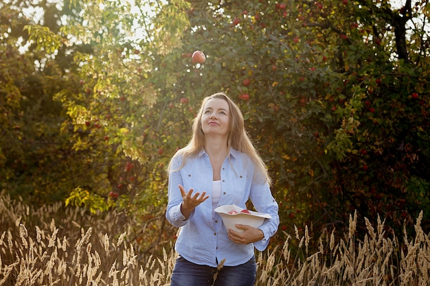 45 year old happy woman throws up an apple in the autumn garden at sunset