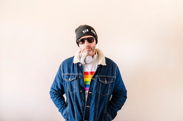 45-year-old man dressed in a white t-shirt with the pride flag, denim jacket and hat.