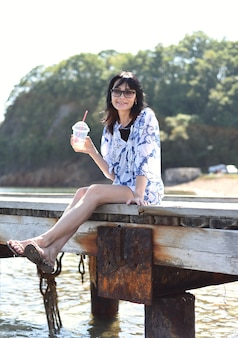 45 years old russian woman drinking lemonad and sitting on pier