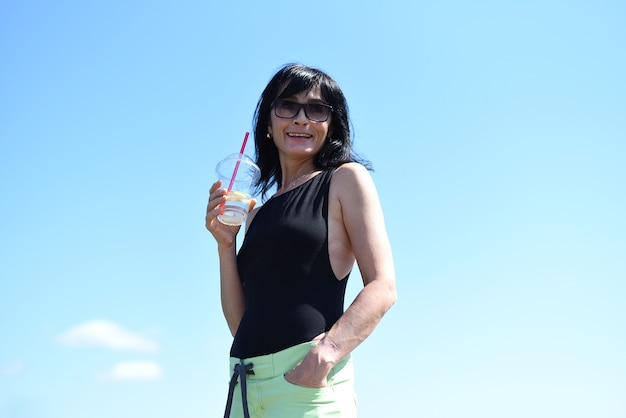 45 years old russian woman drinking lemonad and standing against blue sky