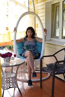 45세 러시아 여성이 잠자는 고양이와 함께 아늑한 베란다에 그네 의자를 걸고 쉬고 있다