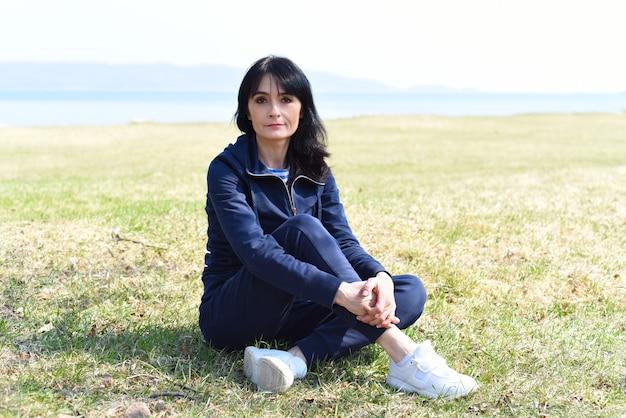 일본 바다의 해변에 앉아 있는 45세 러시아 여성