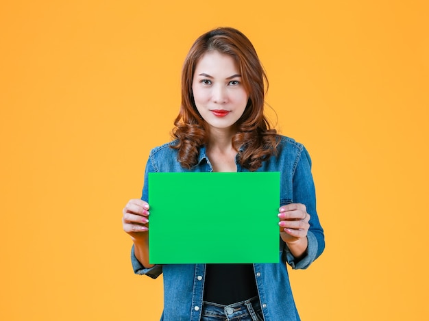 45s cute beautiful curly hair asian woman holding green blank paper cardboard, studio shot with flash light on bright yellow background. idea for advertising content added.