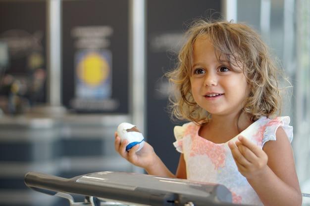 4歳の女の子がスーパーでチョコレートの卵に満足