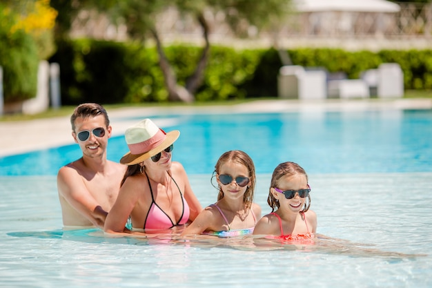 スイミングプールで4人の幸せな家族
