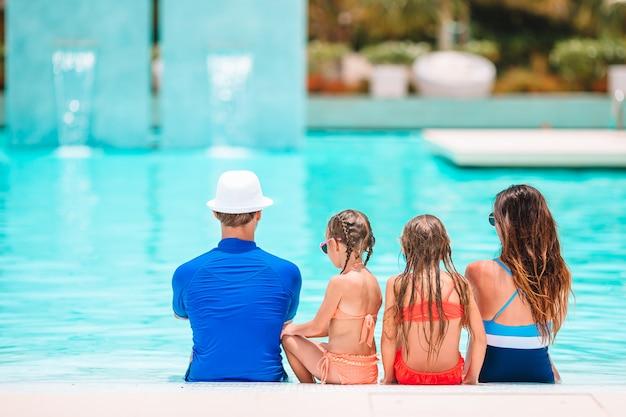 屋外スイミングプールで4つの幸せな家族