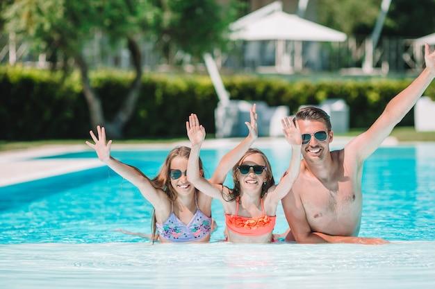 屋外スイミングプールでの4人の幸せな家族