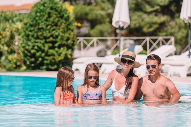 屋外スイミングプールで4人の幸せな家族