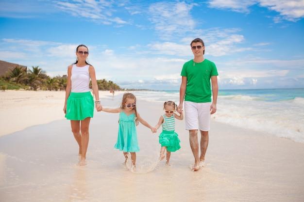 4人の若い美しい家族は、ビーチでリラックスを楽しんだ