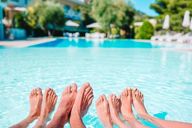 プールサイドで4人の足のクローズアップ