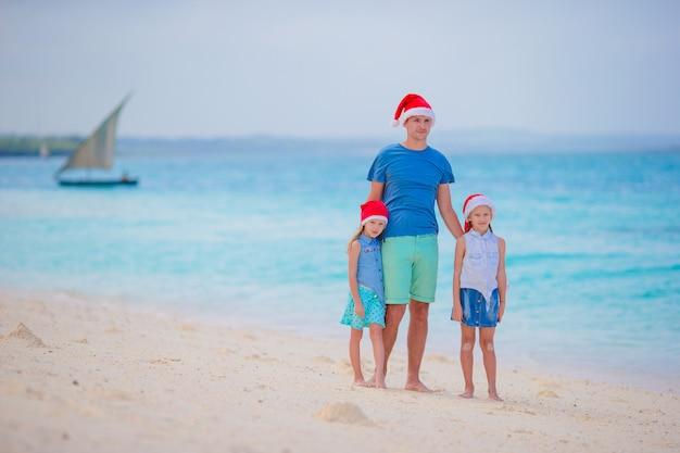 夏休みにサンタ帽子で幸せな家族。海の旅を楽しんでいる4人の若い家族とのクリスマス休暇