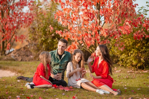 秋の4人の幸せな家族の肖像画
